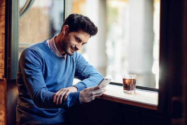 Homem sorridente com camisola azul olhando seu smartphone em um pub moderno.