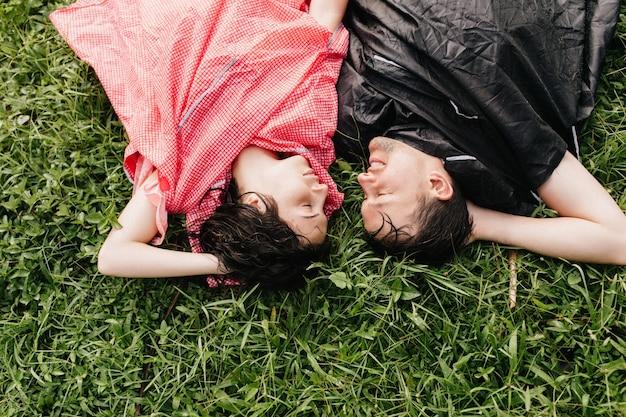 Homem sorridente com capa de chuva preta deitado no chão. jovens cansados, posando na grama com a expressão de rosto feliz.
