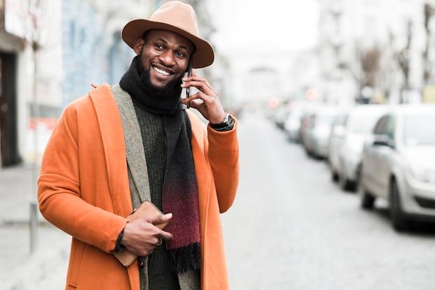 Homem sorridente com casaco laranja, olhando para longe