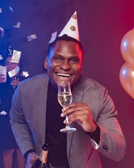 Homem sorridente com chapéu de festa segurando um copo