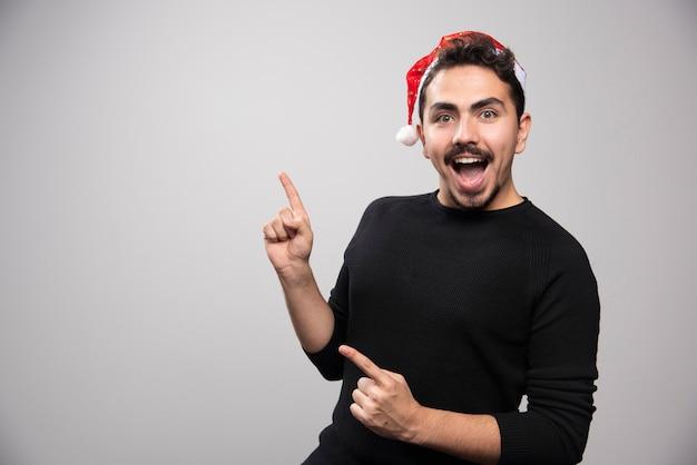 Homem sorridente com chapéu de papai noel aparecendo os dedos.