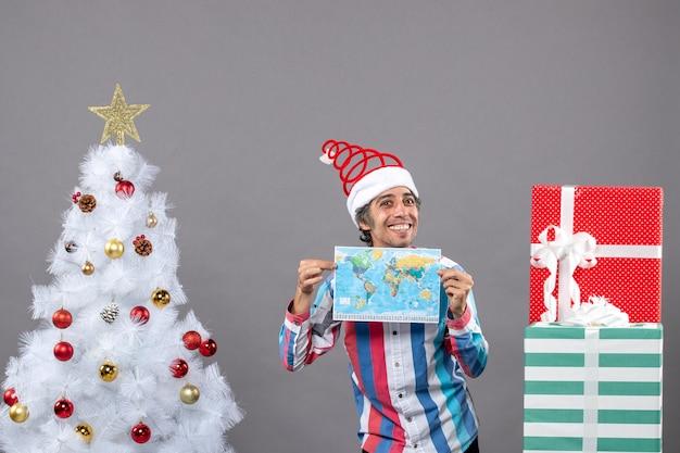 Homem sorridente com chapéu de papai noel com mola espiral segurando o mapa com as duas mãos.