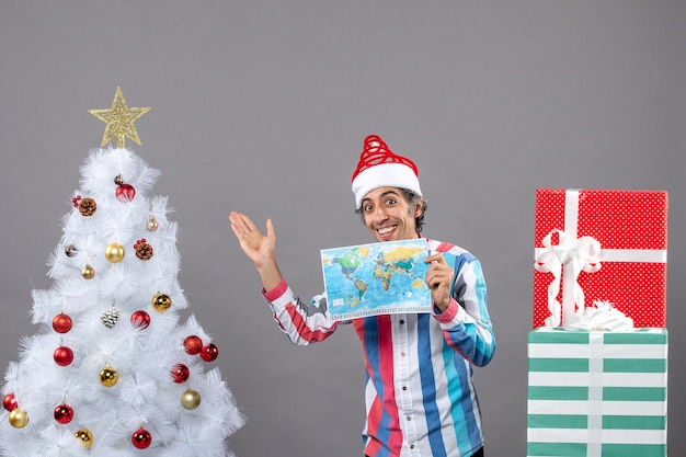 Homem sorridente com chapéu de papai noel com mola espiral segurando o mapa do mundo e apontando para a árvore de natal