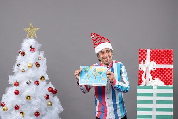 Homem sorridente com chapéu de papai noel espiral e camisa listrada segurando o mapa