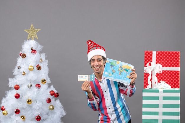 Homem sorridente com chapéu de papai noel segurando um mapa-múndi e uma passagem