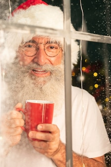 Homem sorridente com chapéu de papai noel segurando uma caneca e olhando pela janela