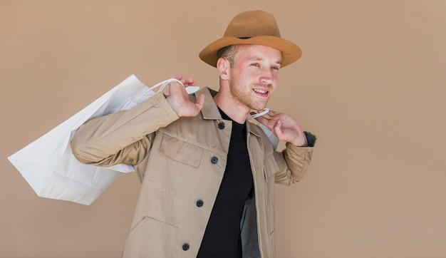 Homem sorridente com chapéu marrom e sacolas de compras