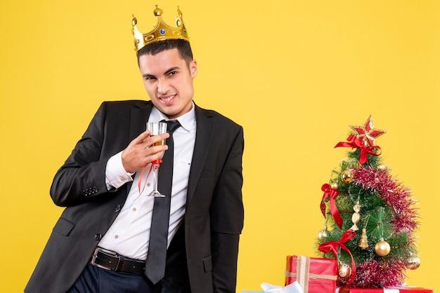 Homem sorridente com coroa segurando um coquetel em pé perto da árvore de natal e presentes