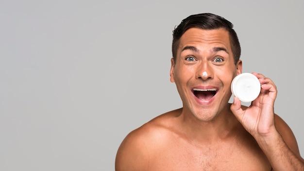 Homem sorridente com creme facial