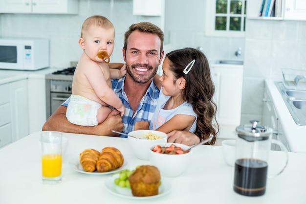 Homem sorridente com dois filhos tomando café na cozinha