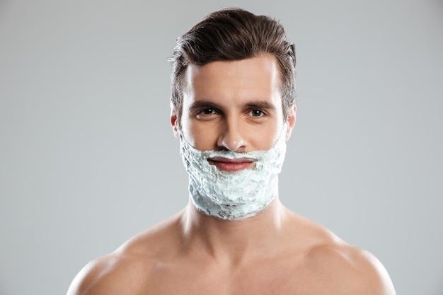 Homem sorridente com espuma de barbear no rosto