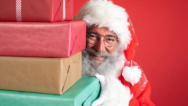 Homem sorridente com fantasia de papai noel segurando presentes