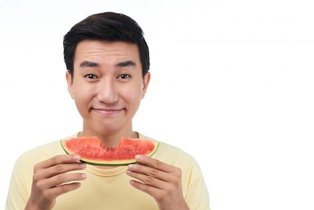 Homem sorridente com fatia de melancia