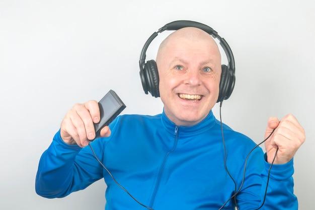 Homem sorridente com fones de ouvido e player digital portátil na mão relaxa enquanto ouve sua música favorita