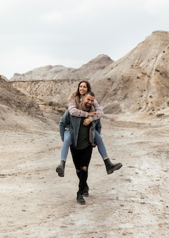 Homem sorridente com foto completa carregando mulher