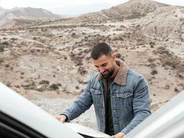 Homem sorridente com foto média segurando mapa