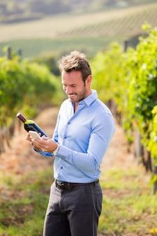 Homem sorridente com garrafa de vinho usando o telefone