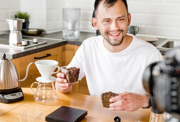 Homem sorridente com grãos de café