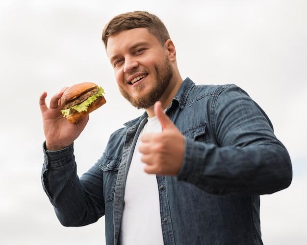 Homem sorridente com hambúrguer mostrando aprovação