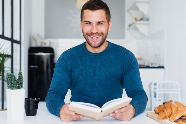 Homem sorridente com livro na mão em casa