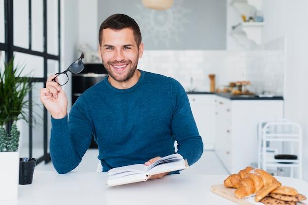 Homem sorridente com livro, olhando para a câmera