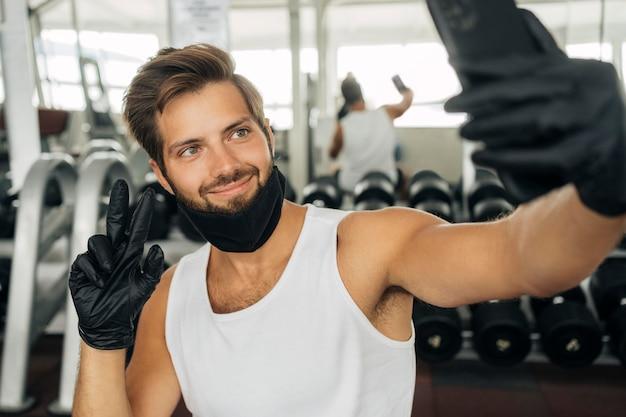 Homem sorridente com máscara médica tirando uma selfie na academia