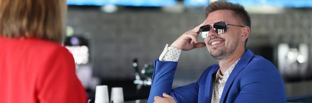 Homem sorridente com óculos de sol se senta no bar perto da mulher.