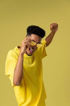 Homem sorridente com óculos escuros tiro médio