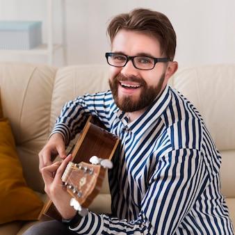 Homem sorridente com óculos tocando violão