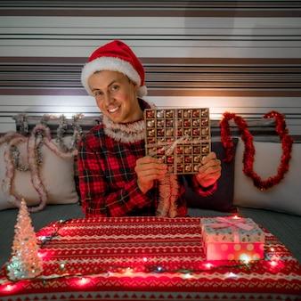 Homem sorridente com presente de natal no quarto