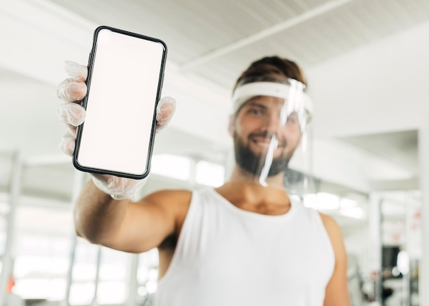 Homem sorridente com protetor facial na academia segurando um smartphone