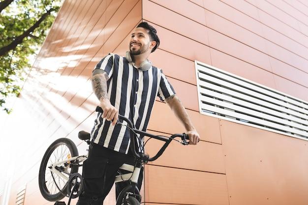 Homem sorridente com roda de bicicleta, sorriso feliz