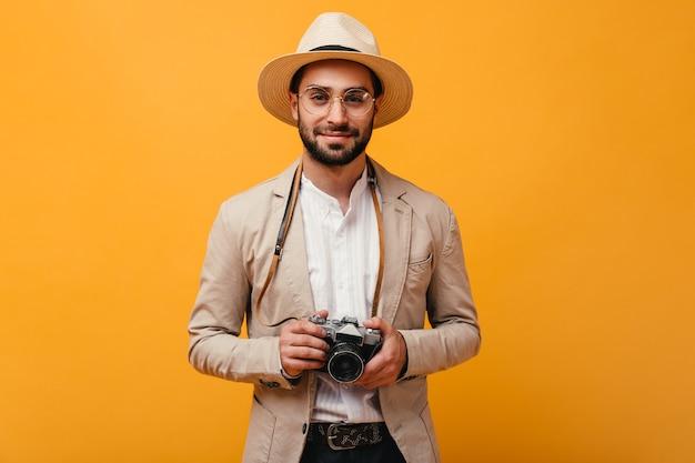 Homem sorridente com roupa bege segurando uma câmera retro na parede laranja