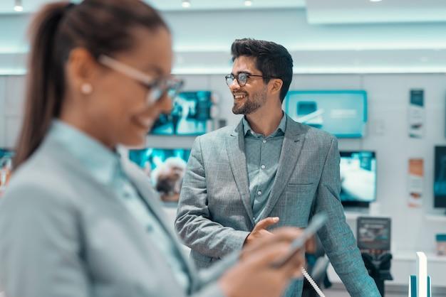 Homem sorridente com roupa formal em pé na loja de tecnologia e desviar o olhar