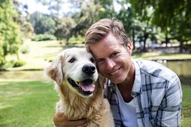 Homem sorridente com seu cão de estimação no parque