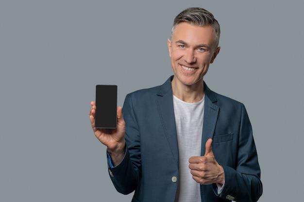 Homem sorridente com smartphone mostrando gesto de ok
