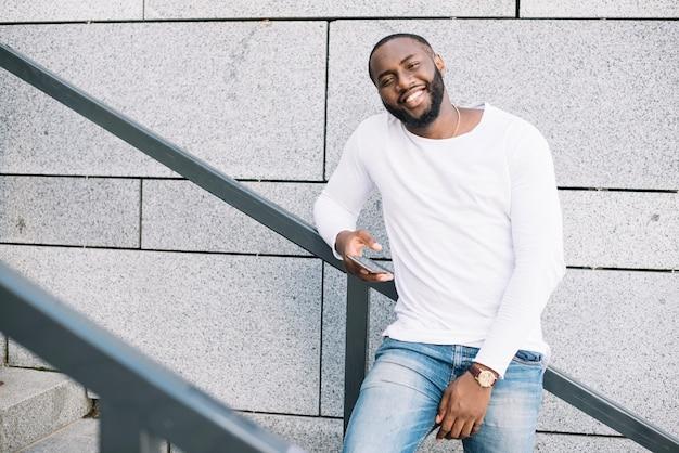 Homem sorridente com smartphone na escada