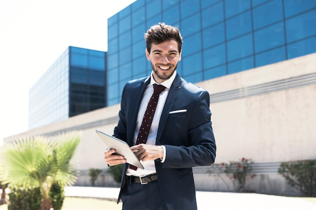 Homem sorridente com tablet, olhando para a câmera