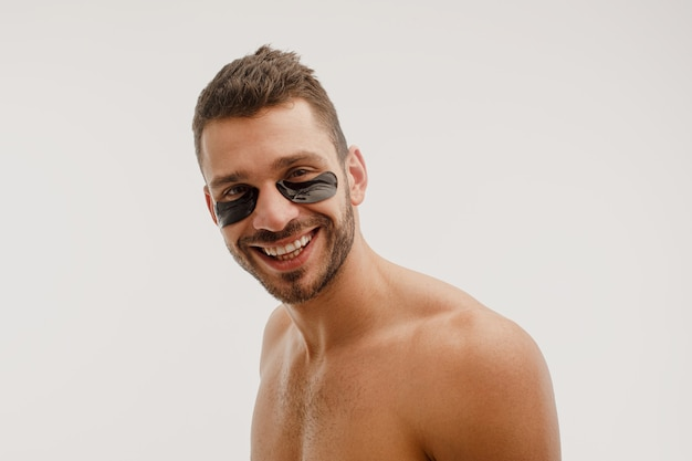 Homem sorridente com tapa-olho no rosto. cara barbudo com a pele perfeita, olhando para a câmera. conceito de cuidados com a pele do rosto. isolado em um fundo branco. sessão de estúdio. copie o espaço