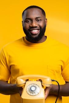 Homem sorridente com telefone antigo