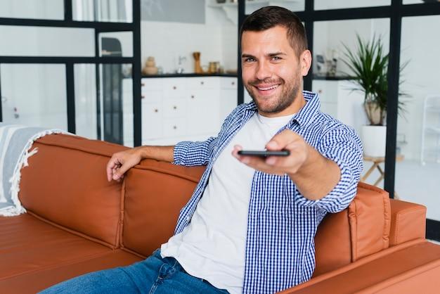 Homem sorridente com telefone na mão no sofá