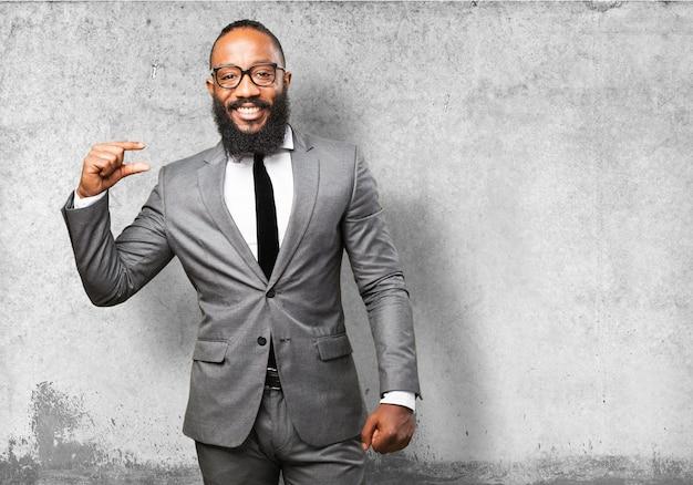 Homem sorridente com terno indicando uma medida com os dedos