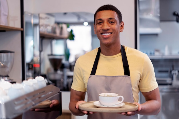Homem sorridente com tiro médio e café