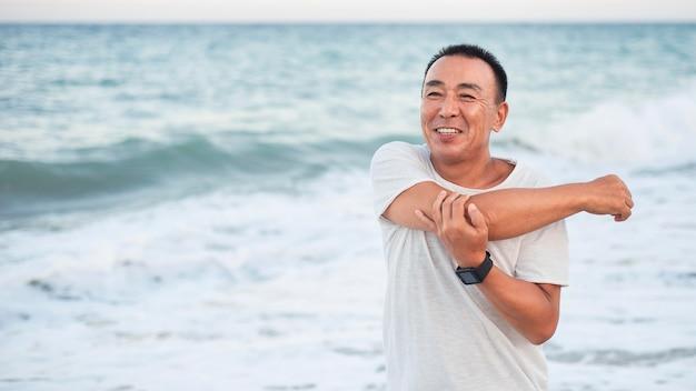 Homem sorridente com tiro médio esticando o braço