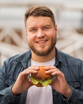 Homem sorridente com tiro médio segurando hambúrguer