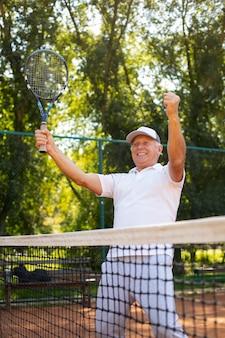 Homem sorridente com tiro médio segurando raquete