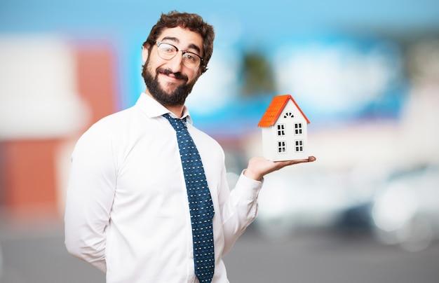 Homem sorridente com uma casa em sua mão