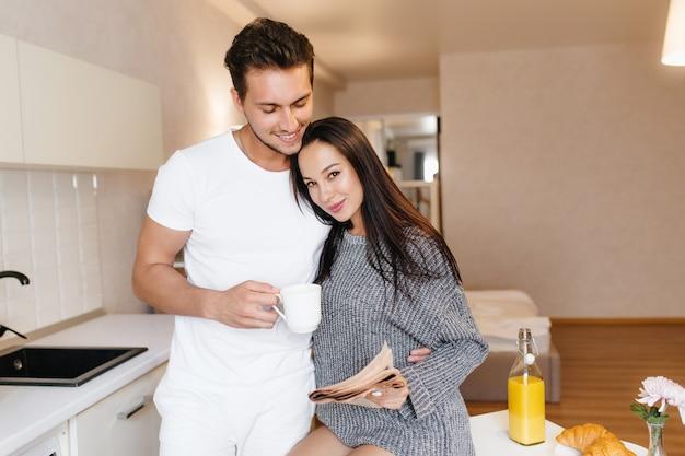 Homem sorridente com uma xícara de café abraçando uma mulher morena segurando um jornal