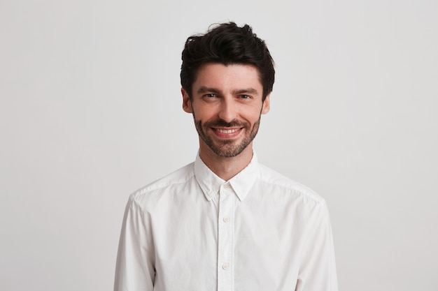 Homem sorridente confiante barbado, vestido de camisa branca casual olha diretamente para a câmera e se sente feliz com seu trabalho.