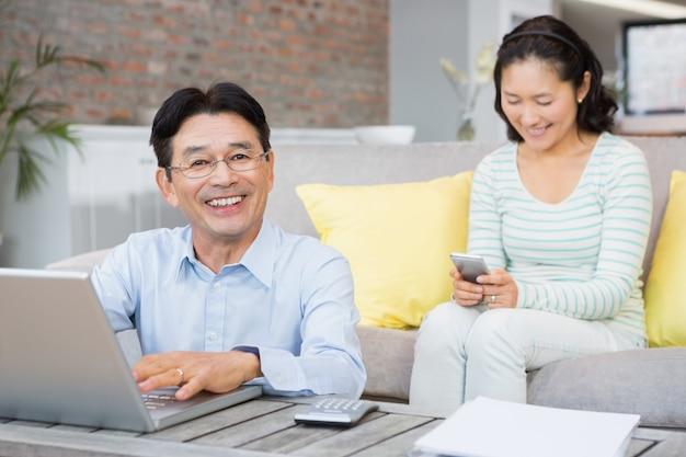 Homem sorridente contando as contas com o laptop na sala de estar